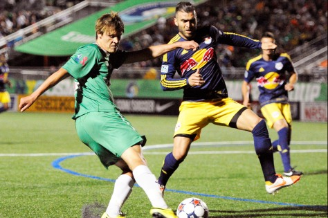 New York Cosmos' Mads Stokkelien kicks the ball against New York Red Bulls' Armando during the U.S. Open Cup soccer game in Hempstead, N.Y., Saturday, June 14, 2014. (AP Photo/Kathleen Malone-Van Dyke)